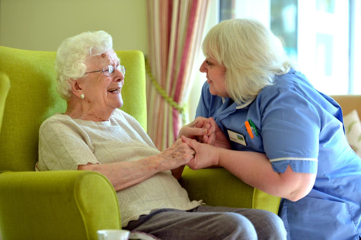 Carer kneeling down smiling at resident who is sitting in a green armchair