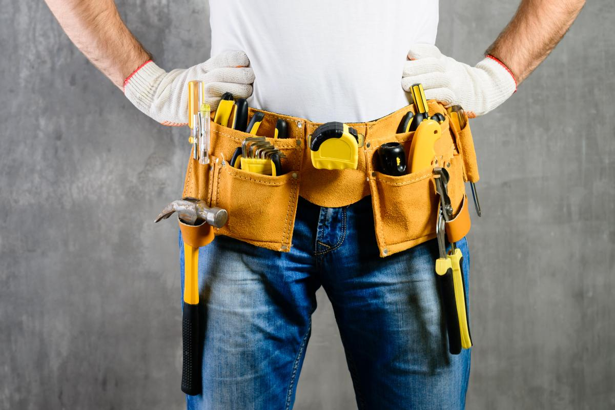Man with hands on hips wearing a tool belt full of tools