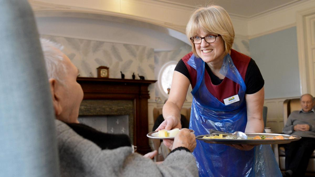 Care assistant offering a tray of fruit to a resident