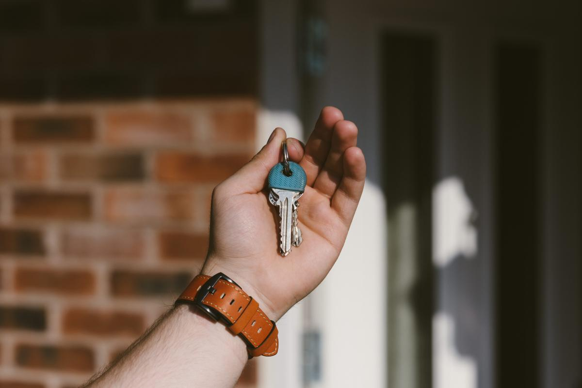 hand holding keys with front door in the background