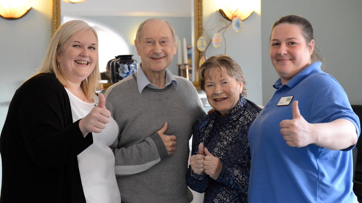 care home manager with two residents and care assistant showing their thumbs up