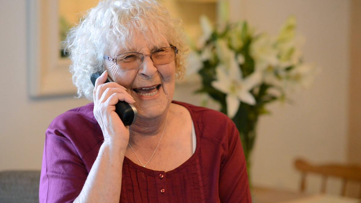 Older lady smiling whilst talking on the telephone