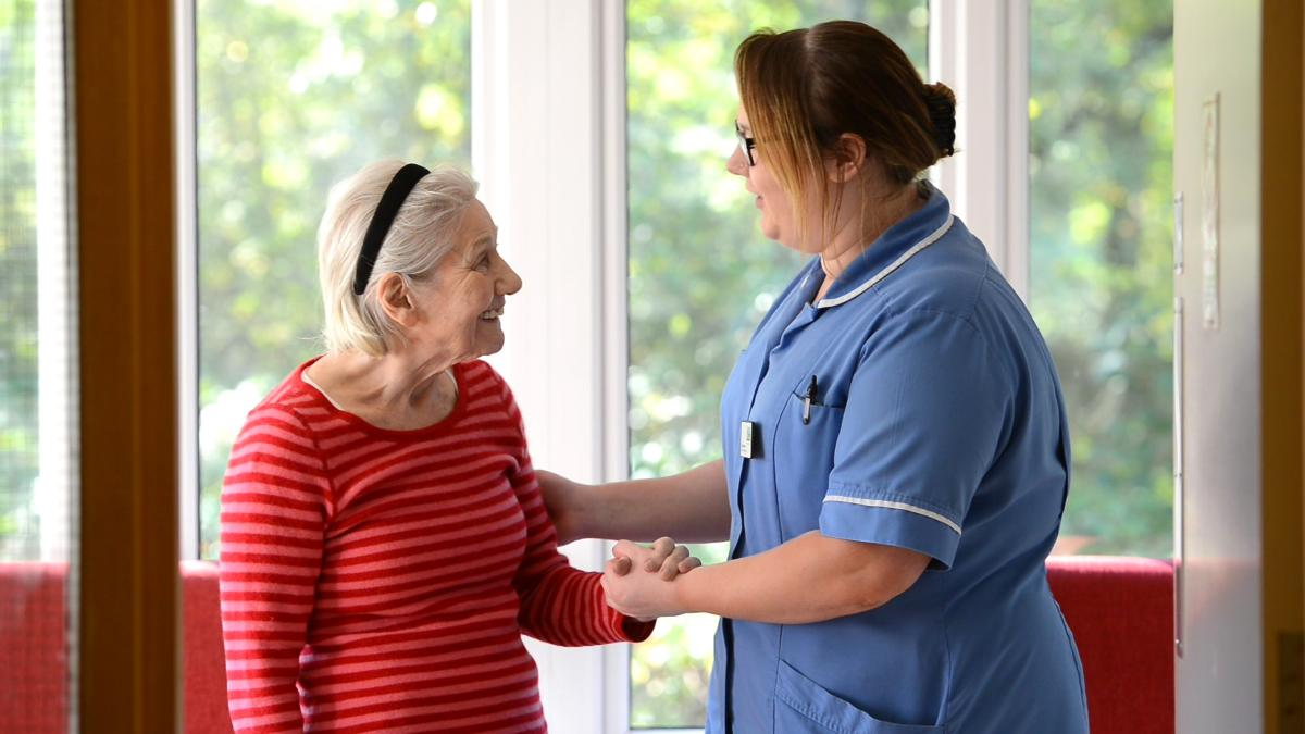 resident and carer standing looking at each other touching their arms