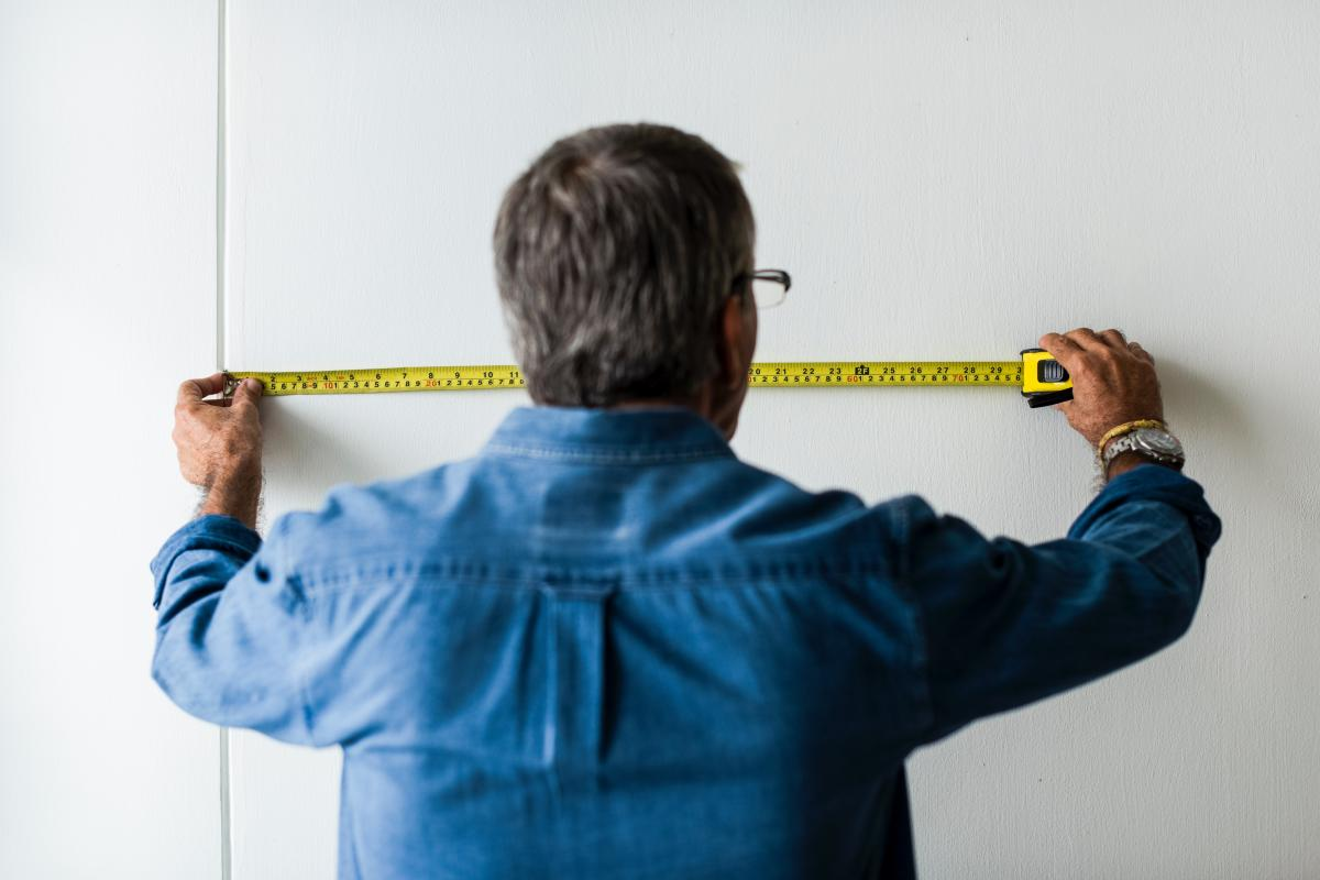 man facing a wall with a horizontal measuring tape on the wall