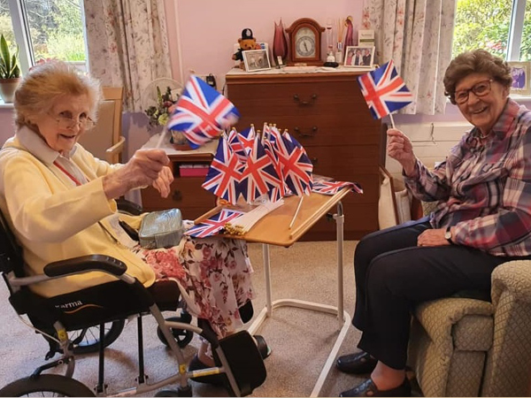 Two residents holding union jack flags looking at the camera and waving