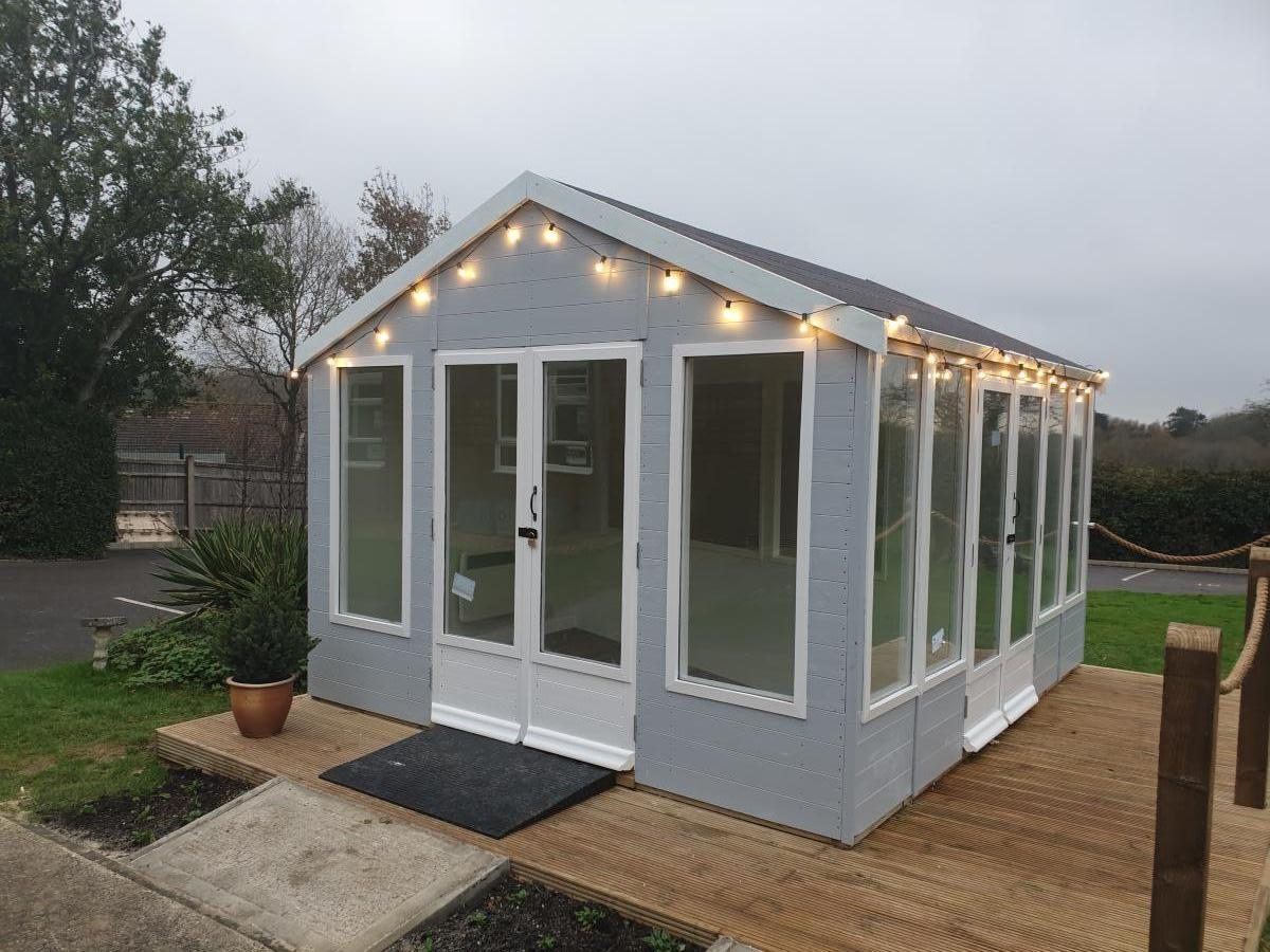 Grey summer house with two entrances and fairy lights