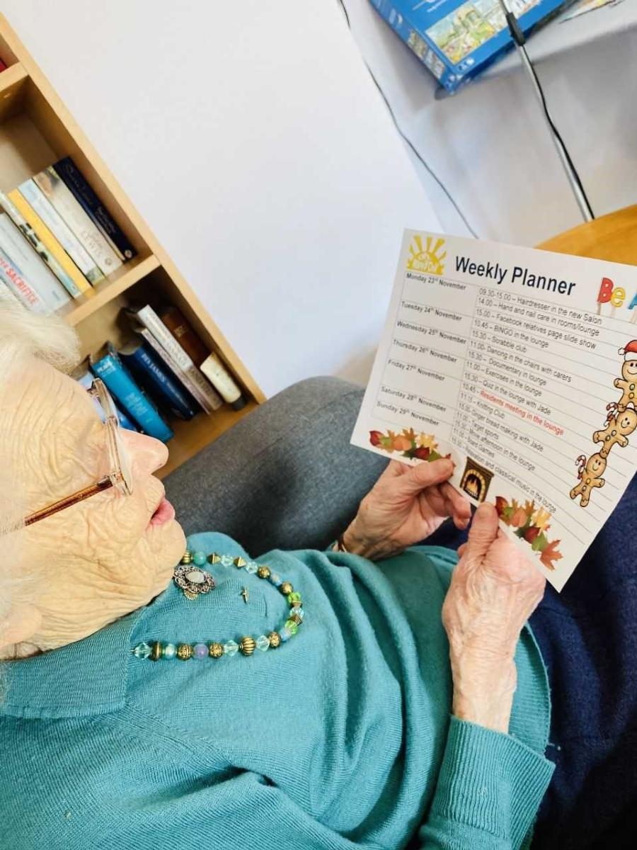 Lady resident looking at the printed weekly activities planner
