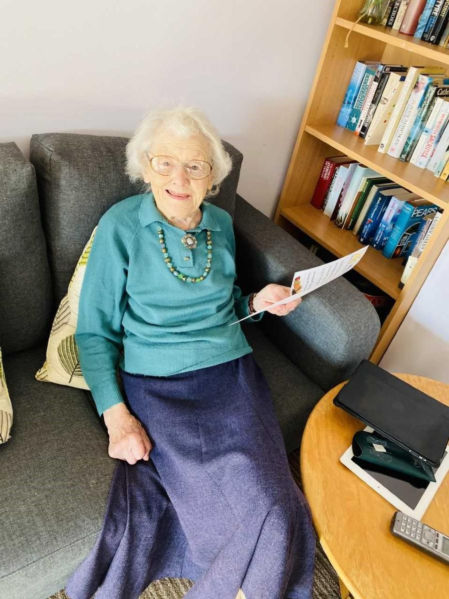 Lady resident sitting on a grey sofa reading activities planner