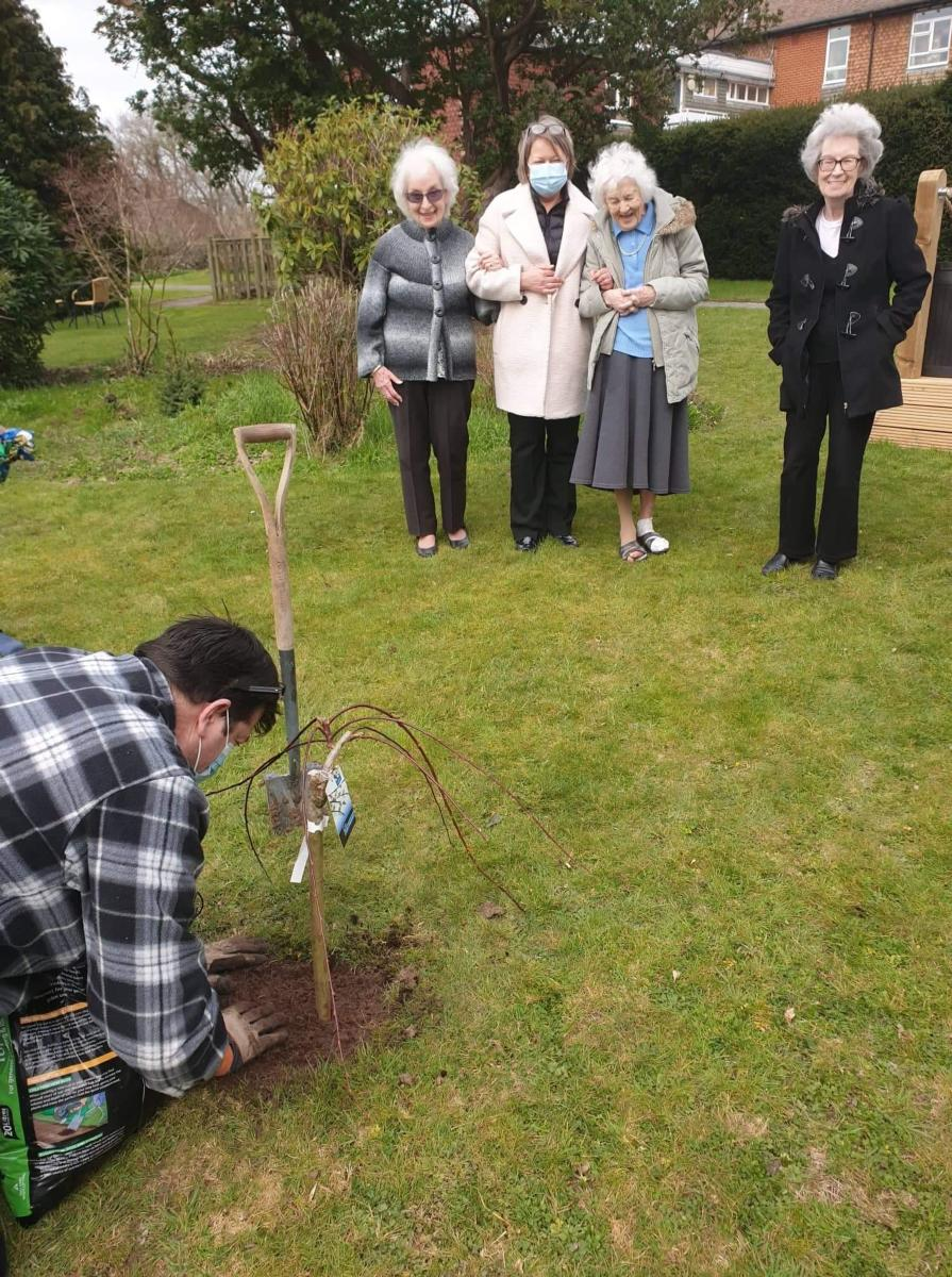 small group of residents in the garden looking at new willow tree being planted