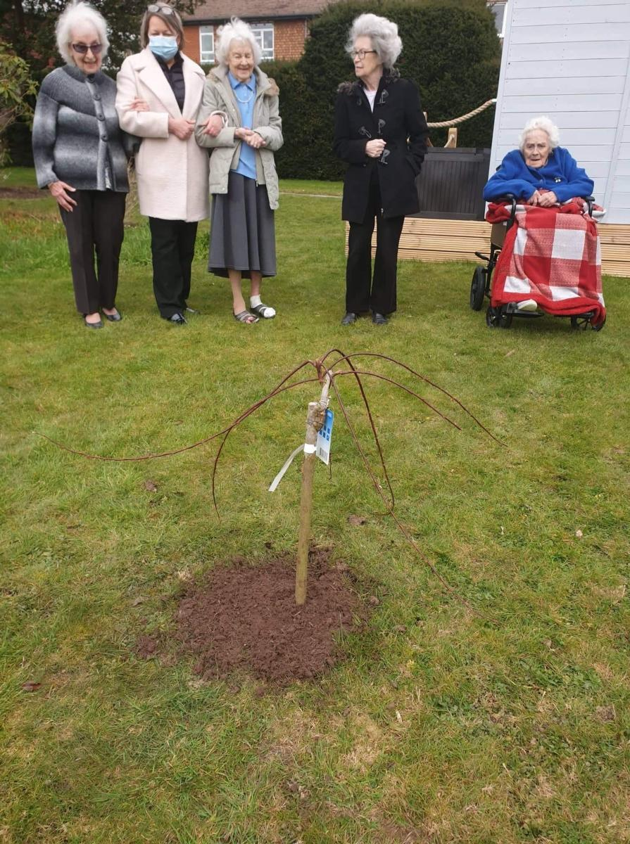 three female residents standing with care home manager looking down at newly planted tree