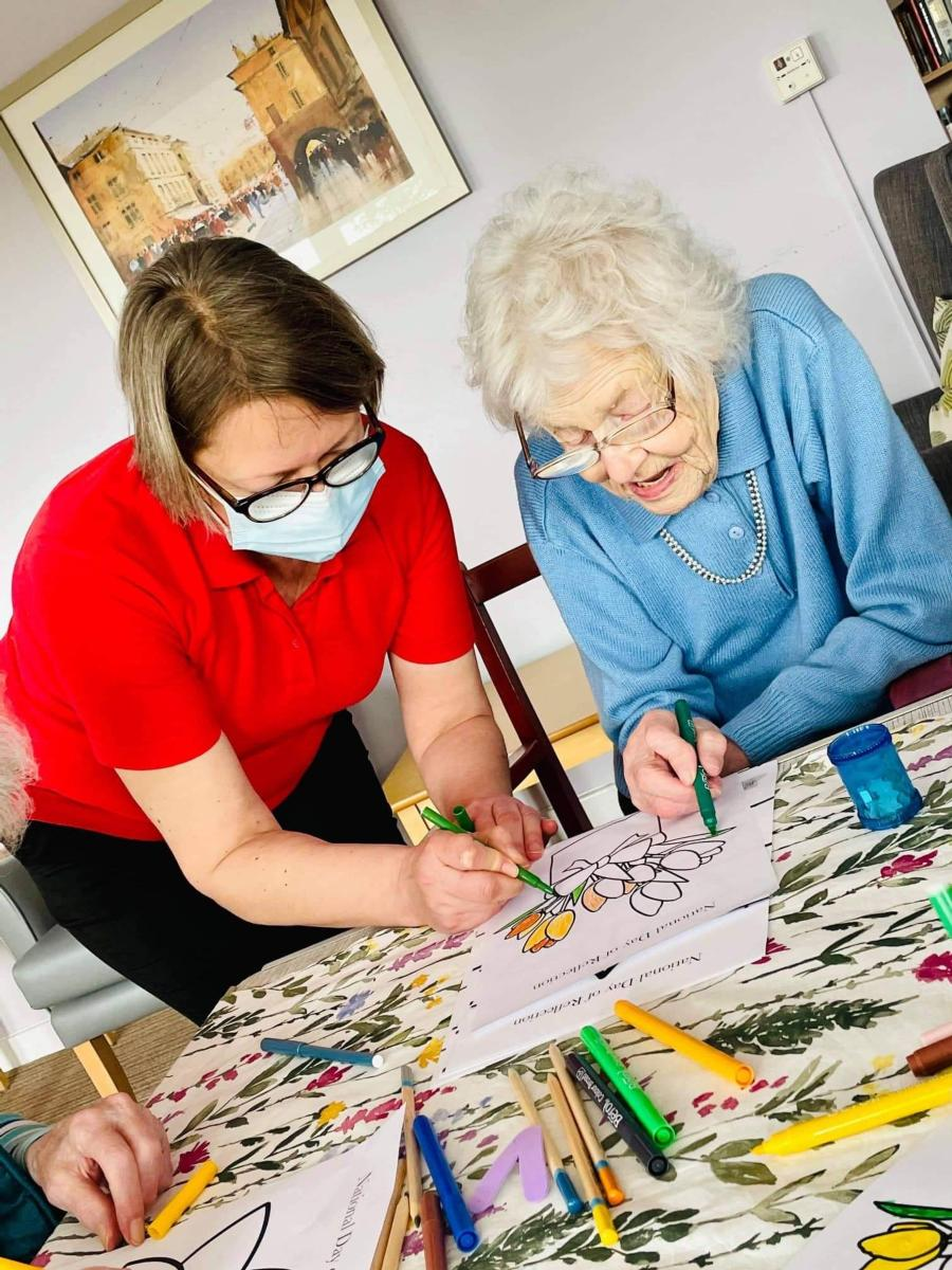 resident colouring at table with care home manager joining in
