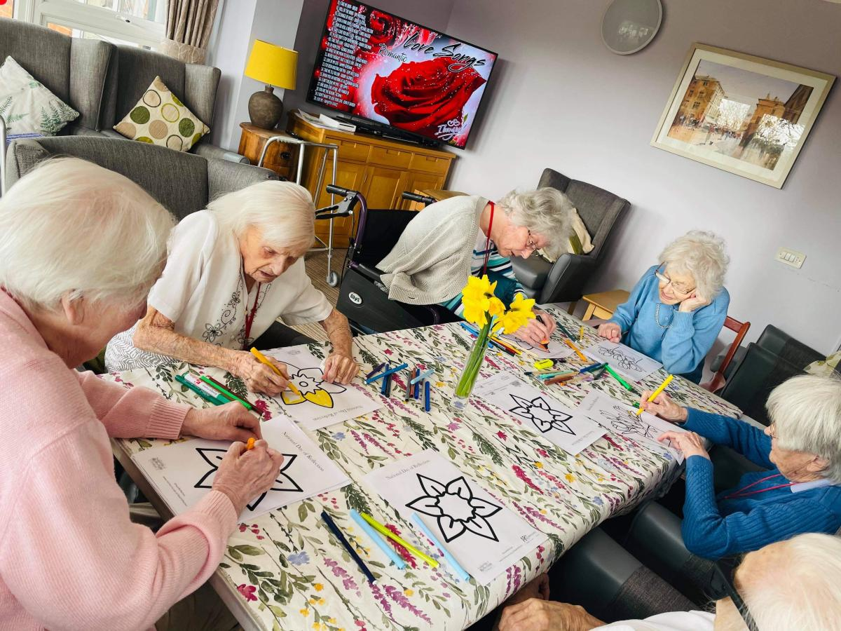 group of residents sat at the table enjoying colouring in
