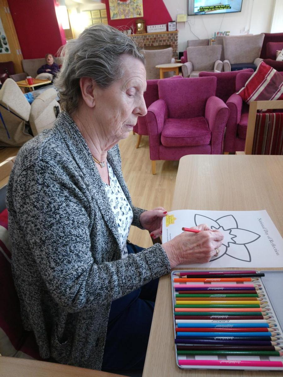 lady sat at table colouring a daffodil drawing
